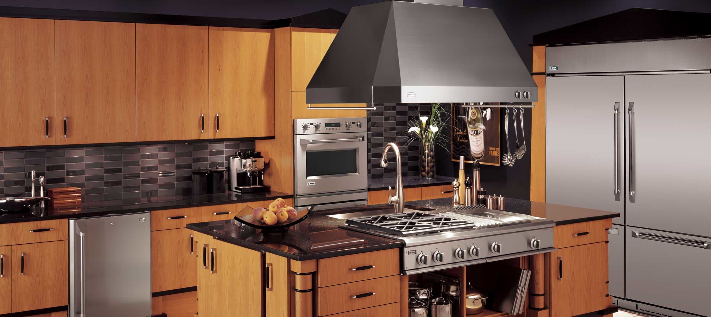 Understated onyx kitchen with a central GE hood.