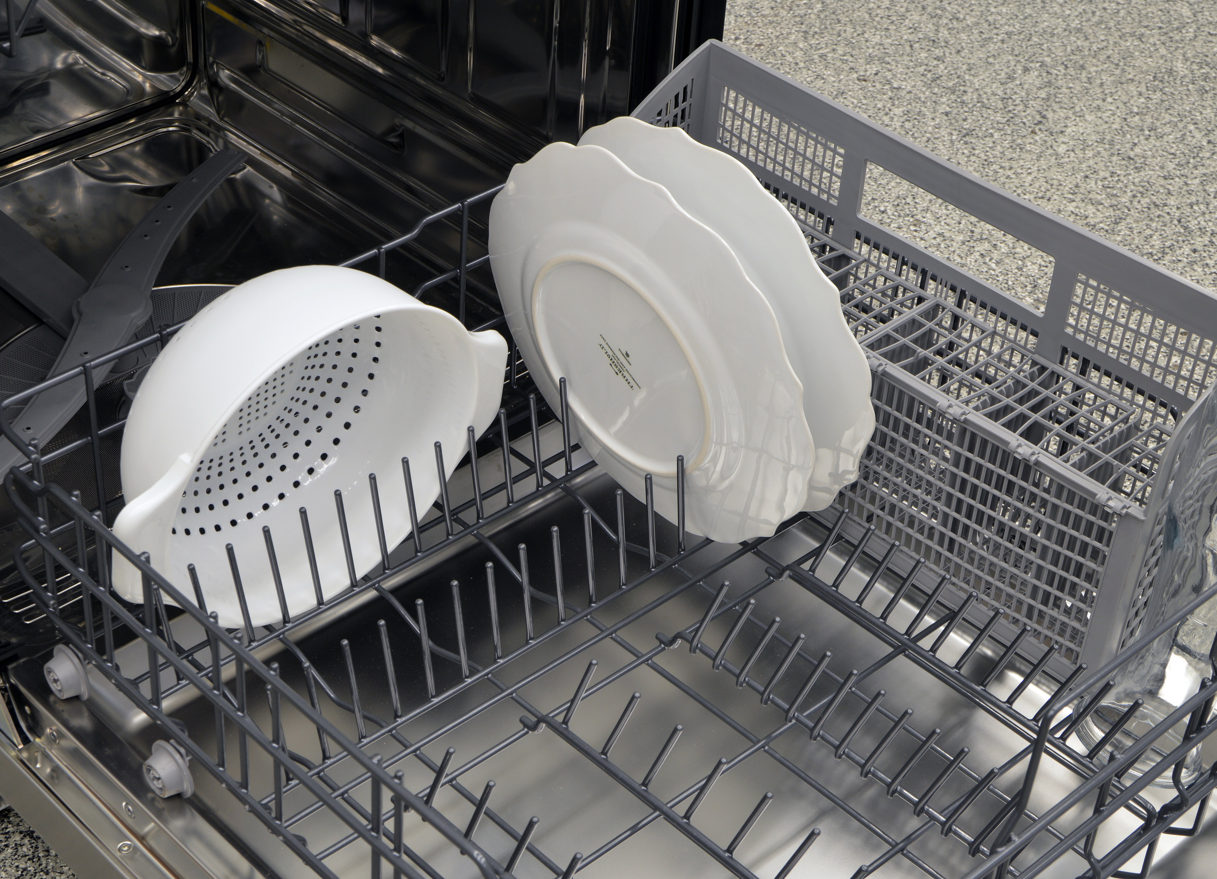 A colander and some thick plates loaded in the lower rack
